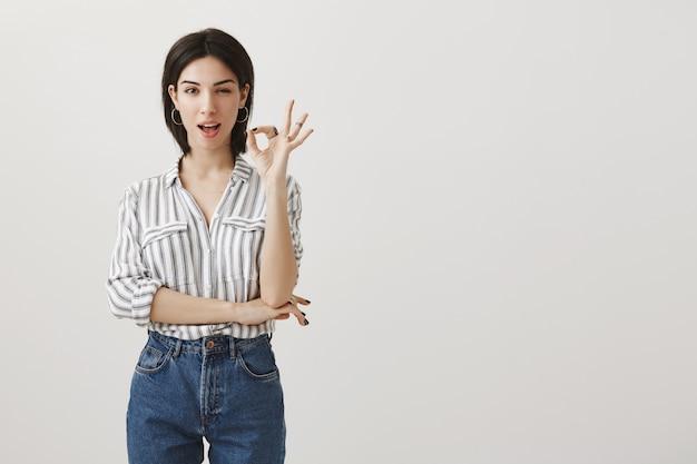 Professionele vrouwelijke ondernemer garandeert al het goede, knipoogt en laat een goed gebaar zien