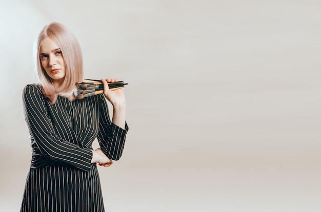 Professionele vrouwelijke stylist met make-upborstels op een beige achtergrond