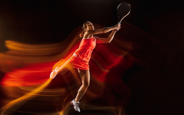 Professionele vrouwelijke tennisspeelster training geïsoleerd op zwarte studio achtergrond in gemengd licht. vrouw in sportpak oefenen.