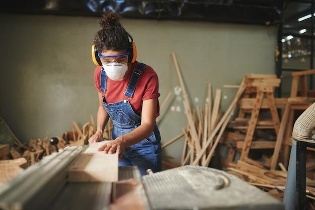 Professionele vrouwelijke timmerman in beschermende brillen, oorkappen en masker houten plank snijden op tafelzaag