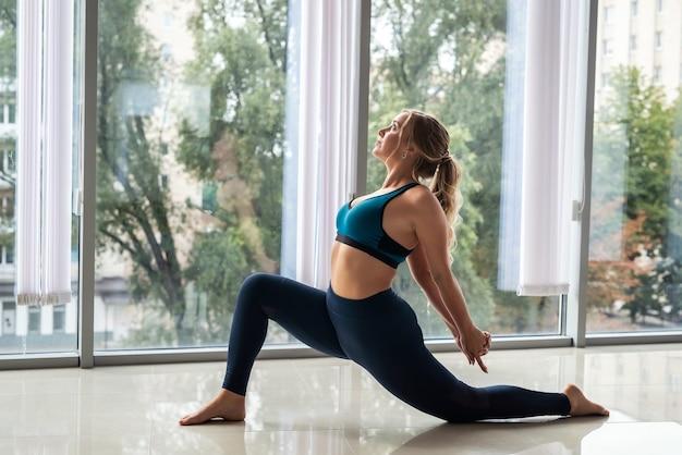 Professionele vrouwelijke trainer die ontspannen yoga doet die binnenshuis uitoefent. fit en gezonde levensstijl.