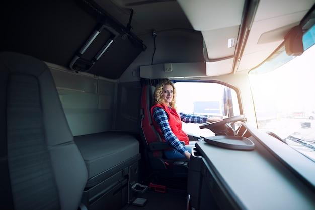 Professionele vrouwelijke vrachtwagenchauffeur zit in de vrachtwagen.