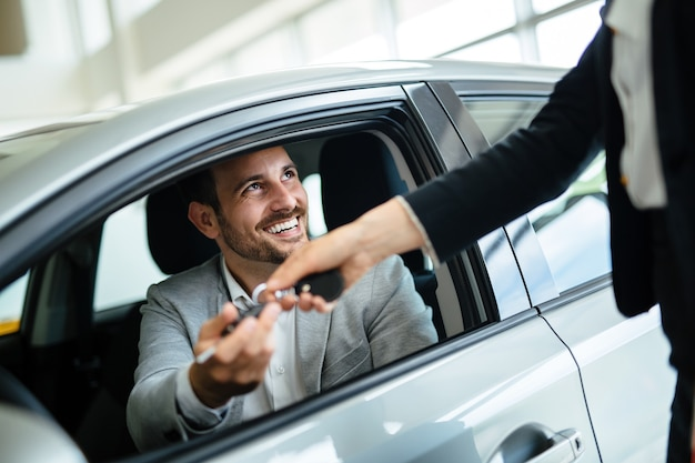 Professionele vrouwenverkoper tijdens het werk met klant bij autodealer.