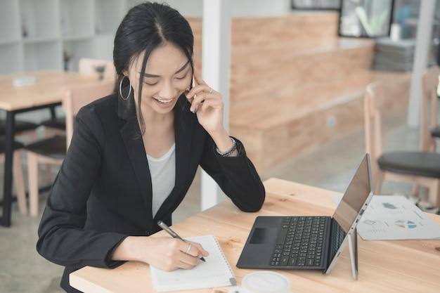 Professionele werkende vrouw die met mobiele telefoon en writngdocument spreekt voor de lijst van informatiegegevens. werken op kantoor met technologie concept.