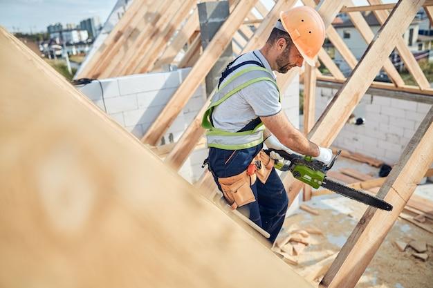 Professionele werker van een bouwplaats die een veiligheidshelm draagt en een elektrische kettingzaag start om wat hout te zagen