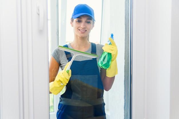 Professionele werknemer van schoonmaakbedrijf wast raam met een wisser en wasmiddelen in een modern appartement met speciale uniformen en gele rubberen handschoenen.