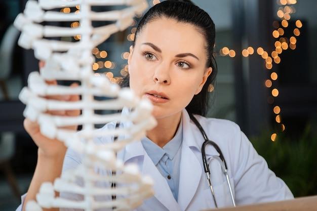 Professionele wetenschapper. slimme aardige mooie vrouw die naar het dna-model kijkt en het bestudeert terwijl ze werkt als een genetische wetenschapper