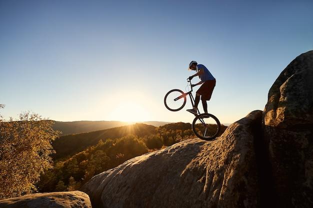 Professionele wielrenner balanceren op proeffiets bij zonsondergang