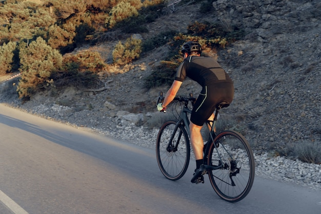Professionele wielrenner op een bergweg bij zonsopgang
