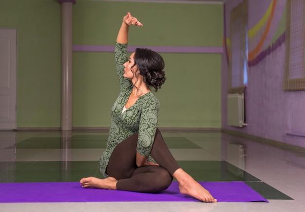 Professionele yoga trainer yoga asana tonen in fitness klasse.