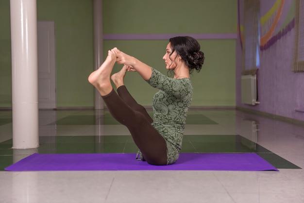 Professionele yogatrainer beoefent yogales in de sportschool.