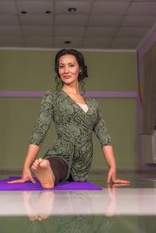 Professionele yogatrainer vormt in de fitnessklasse