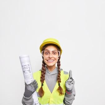 Professionele ypung-vrouweningenieur geeft aanbevelingen over huisverbetering komt op de bouwplaats om haar bouwideeën te presenteren, houdt een blauwdruk vast die aangeeft dat ze veiligheidskleding draagt.