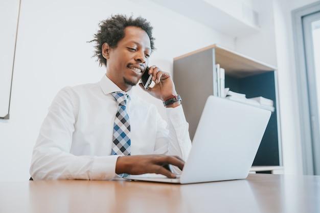 Professionele zakenman die aan de telefoon praat en zijn laptop gebruikt terwijl hij op kantoor werkt. bedrijfsconcept
