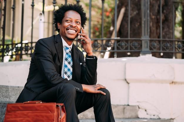 Professionele zakenman die aan de telefoon praat terwijl hij buiten op de trap zit. bedrijfs- en technologieconcept.
