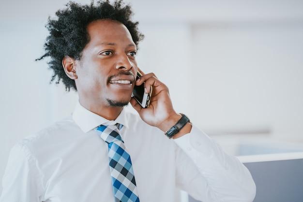 Professionele zakenman die aan de telefoon praat terwijl hij op een modern kantoor werkt. bedrijfsconcept.