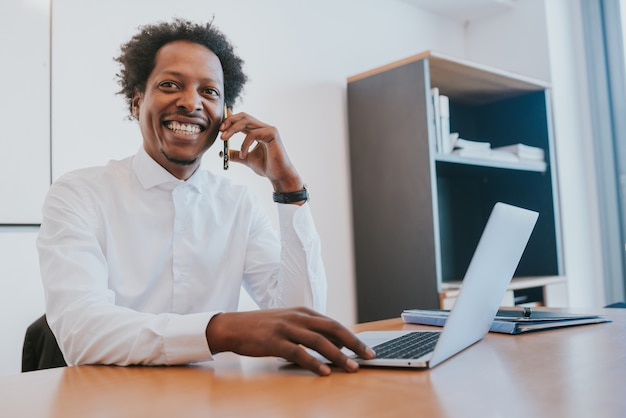 Professionele zakenman die aan de telefoon praat terwijl hij op zijn moderne kantoor werkt. bedrijfsconcept.