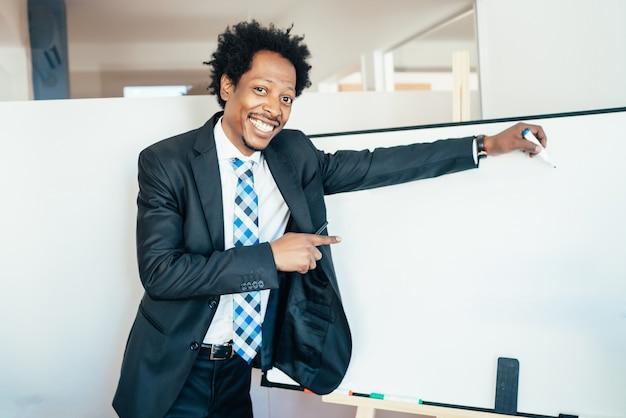 Professionele zakenman die iets op leeg whiteboard toont of richt