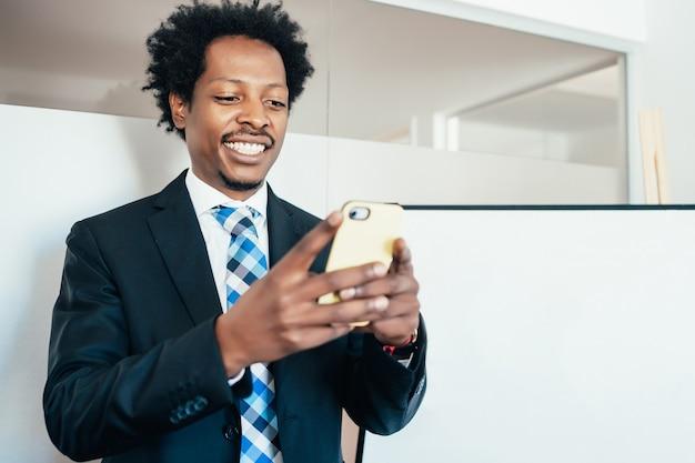 Professionele zakenman die zijn mobiele telefoon gebruikt terwijl hij op kantoor werkt. bedrijfsconcept.