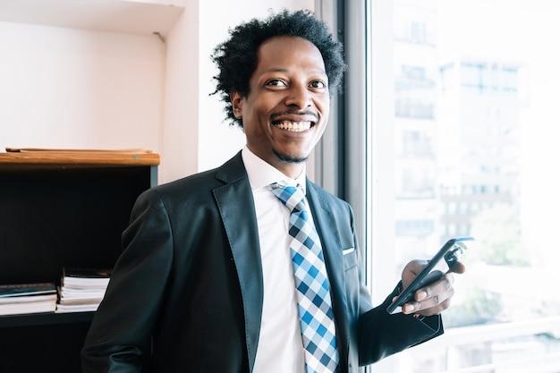 Professionele zakenman die zijn mobiele telefoon gebruikt terwijl hij op kantoor werkt