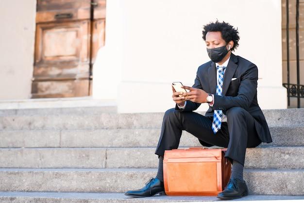 Professionele zakenman gezichtsmasker dragen en het gebruik van zijn mobiele telefoon zittend op de trap buiten op straat. nieuwe normale levensstijl. bedrijfsconcept.