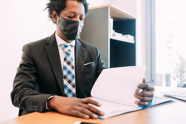 Professionele zakenman gezichtsmasker dragen tijdens het werken met sommige bestanden en documenten op zijn kantoor.