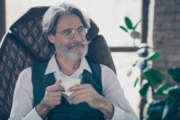 Professionele zakenman koffiekopje houden op industriële kantoor loft