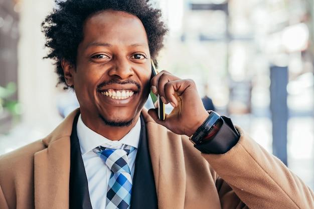 Professionele zakenman praten aan de telefoon tijdens het wandelen buiten op straat. bedrijfsconcept.