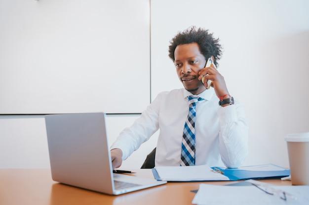 Professionele zakenman praten aan de telefoon tijdens het werken op zijn kantoor. bedrijfsconcept.