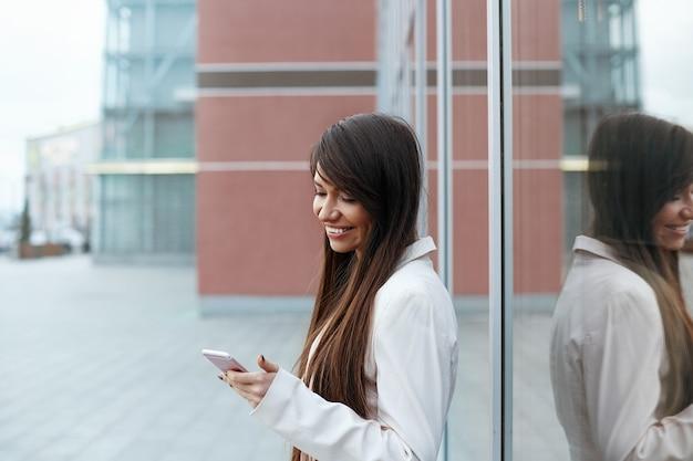 Professionele zakenvrouw met behulp van haar smartphone buitenshuis