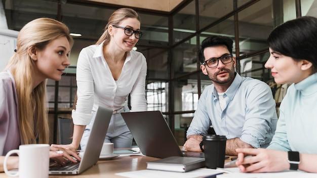 Professionele zakenvrouw met bril tijdens een ontmoeting met haar team