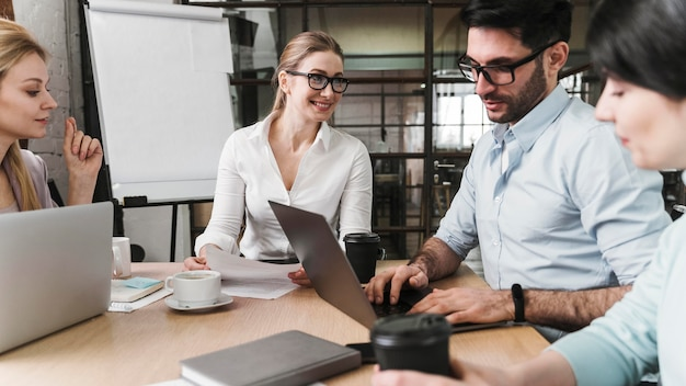 Professionele zakenvrouw met bril tijdens een ontmoeting met haar teamgenoten