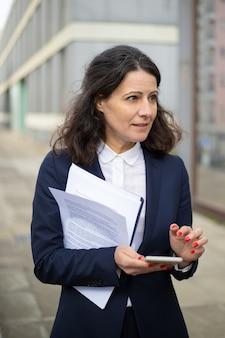 Professionele zakenvrouw met smartphone en papieren