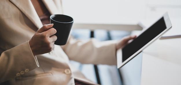 Professionele zakenvrouw werkt aan haar project terwijl het drinken van een kopje koffie
