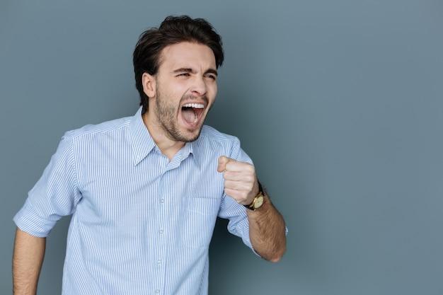 Professionele zangeres. vrolijke positieve getalenteerde man die een microfoon vasthoudt en een lied zingt tijdens het optreden op het podium