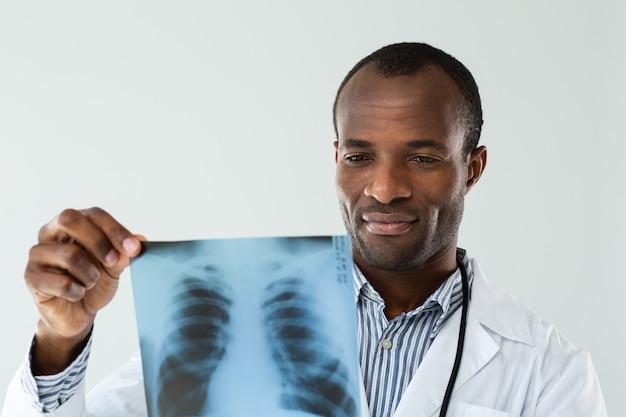 Professionele zelfverzekerde arts die een röntgenscan houdt tijdens het werken