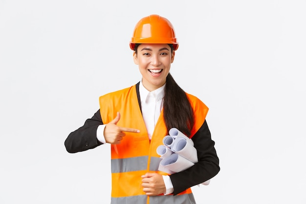 Professionele zelfverzekerde aziatische vrouwelijke architect, hoofdingenieur in veiligheidshelm wijzende vinger naar blauwdrukken, projectplan of documenten voor constructie, staande witte muur.