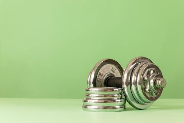 Professionele zware halter met pannenkoeken op een groene achtergrond. fitness of bodybuilding concept achtergrond.