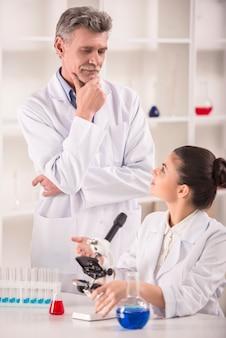 Professor en zijn assistent werkzaam in laboratorium.