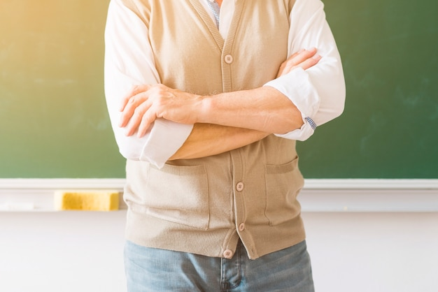 Professor met gekruiste armen staande tegen schoolbord