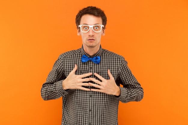Professor uitdrukken die naar de camera kijkt die hart vasthoudt en met grote ogen naar de camera kijkt