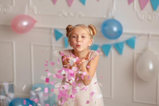 Proficiat met je verjaardag portret van een vrolijke schattige blonde 7-8 jaar oud in een feestelijk decor met confetti en geschenken.