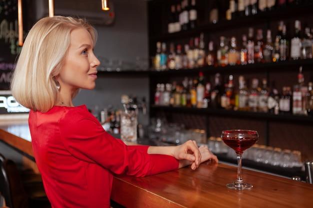 Profiel dat van een schitterende elegante blonde vrouw is ontsproten die rode kleding draagt bij de bar, exemplaarruimte. prachtige vrouw met een drankje aan de bar