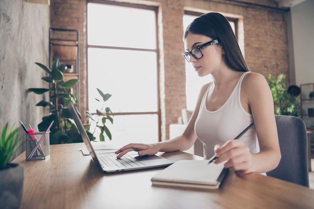 Profiel kant gericht meisje zitten bureaustoel werken op afstand laptop schrijven blocnote