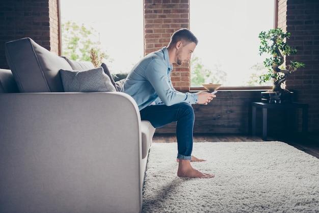 Profiel knappe blote voeten man verblijf thuis quarantainetijd telefoon