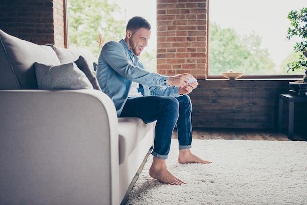 Profiel knappe kerel houdt telefoon handen spelen van videogame