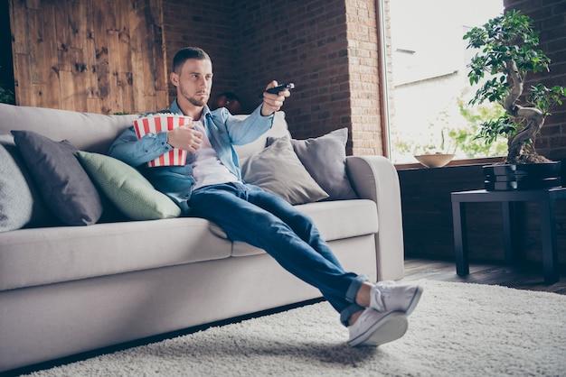 Profiel knappe man ontspannen verblijf thuis eten popcorn zitten gezellige bank