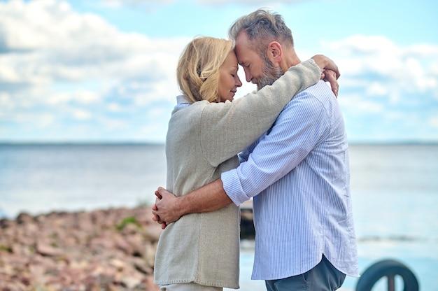 Profiel man en vrouw staan knuffelen