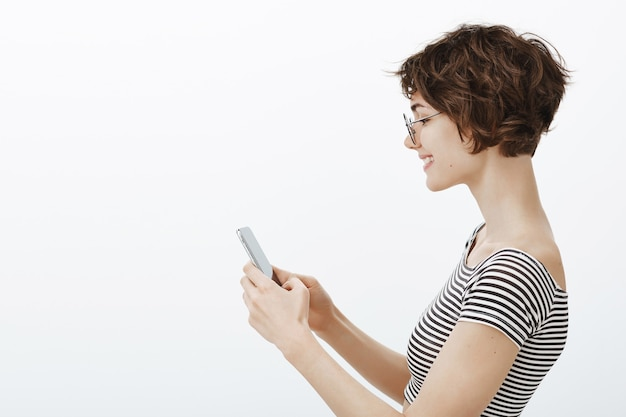 Profiel portret van aantrekkelijke hipster vrouw dating app, messaging op smartphone of met behulp van app