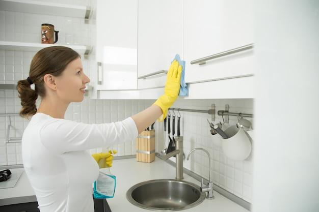 Profiel portret van aantrekkelijke vrouw schoonmaak witte keuken clos
